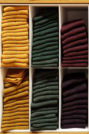 Shelves with evenly folded pullovers in different colors.