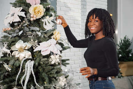 smiling black girl with curly hair decorates Christmas tree with colored balls and ribbons against white wall Stok Fotoğraf
