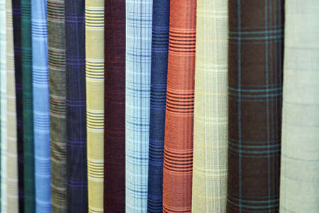 Vertically hanging samples of multi-colored fabric close-up