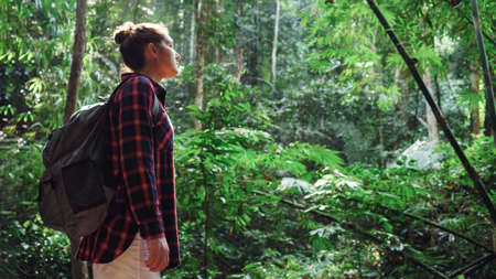 Young woman in a plaid shirt and with a backpack in a rainforest copy space.