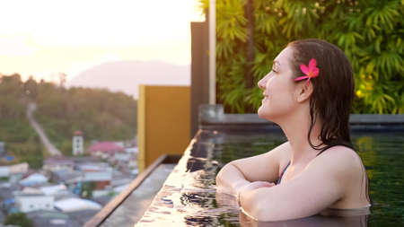 Pretty girl with purple flower in wet hair standing at hotel swimming pool copy space Stok Fotoğraf