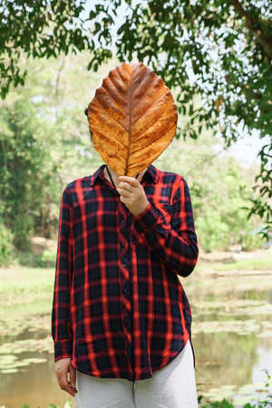 Young woman in a checkered shirt in black and red covers her face with a large, dried leaf of a tree. Stok Fotoğraf