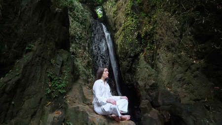 concentrated woman with loose dark hair in white costume meditates sitting in yoga lotus position on rock against tropical waterfall Stok Fotoğraf