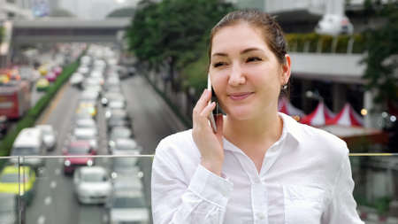 smiling girl talks on smartphone standing on bridge on the close-up copyspace