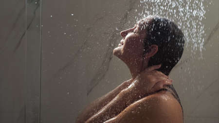 young woman runs hands on face and hair standing under shower water jets behind bathroom cabin glass close view Stok Fotoğraf