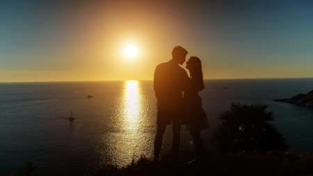 couple silhouettes stand on beach edge and kiss admiring pictorial sunset reflecting in calm ocean water in evening