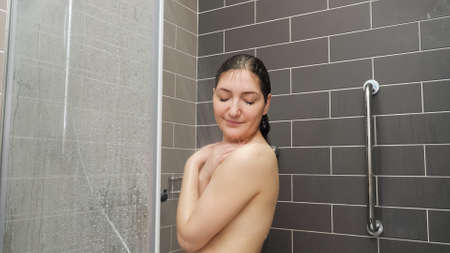 pretty girl w stands under shower and enjoying in tiled bathroom at home closeup Stok Fotoğraf