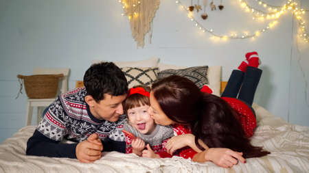 positive parents lie on cozy bed and kiss cute daughter with candy posing at family Christmas closeup