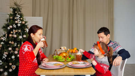 happy husband and wife eat sitting at festive dinner with little daughter by Christmas tree at home