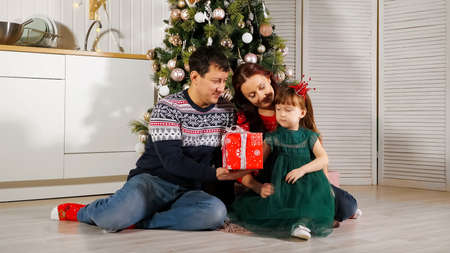 girl child in green dress unpacks New Year gift box sitting at Christmas tree with parents and getting kisses