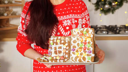 long haired woman poses holding gingerbread house against kitchen furniture and Christmas decorations close-up