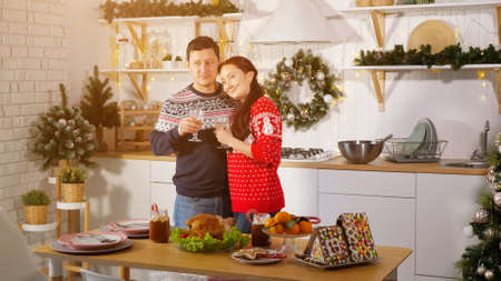 cheerful family couple in Christmas style outfit drinks champagne and hugs showing love in decorated kitchen