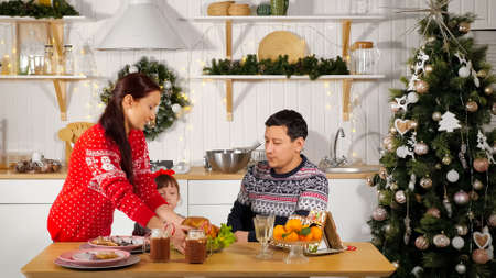 careful mother in red sweater sets table preparing for celebration and father with daughter waits for dinner in kitchen