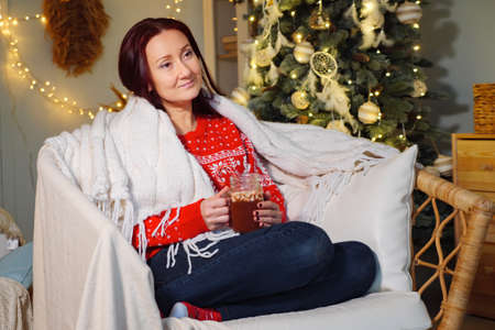 calm brunette woman sits in armchair wrapping in white cozy plaid drinks hot beverage enjoying festive atmosphere