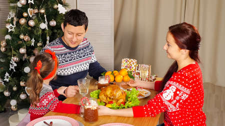 family joins hands and congratulates for Happy New Year telling wishes at festive supper near Christmas tree