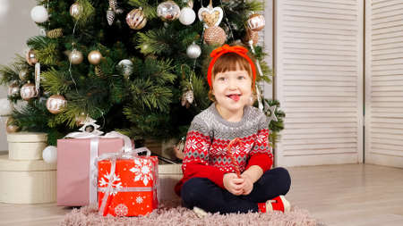 cheerful kid girl sits under decorated Christmas tree with gift boxes holds candy laughing and shows tongue