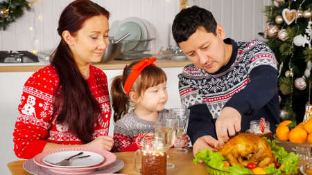 man cuts cooked fried chicken to feed family sitting at holiday table against New Year decorations closeup Stok Fotoğraf