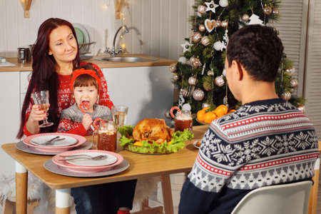 happy husband and wife eat sitting at festive dinner with little daughter by Christmas tree at home close-up