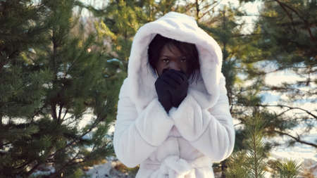 sad dark-skinned girl in hood trembles with cold and warms hands against green pine-trees in cold winter closeup Stock Photo