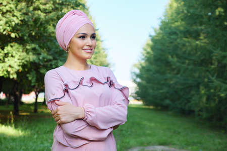 Young muslim woman in pink dress and turban on a background of green trees, copy space. Zdjęcie Seryjne