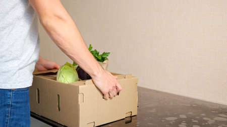 Delivery service man puts cardboard box with vegetables on grey table against white background side view closeup