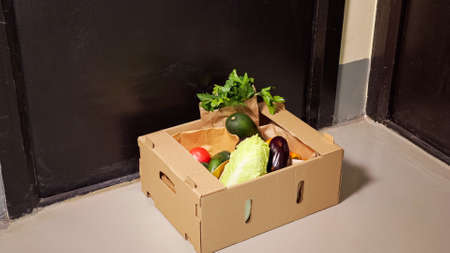 Skilled delivery guy in denim jeans puts brown cardboard container with fresh vegetables on floor near black door closeup Zdjęcie Seryjne
