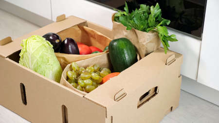 man puts brown cardboard container with various vegetables on floor at kitchen close-up