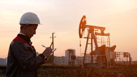 man in overalls fills paper with a pen against the background of an oil pump at sunset. Imagens
