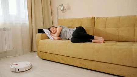 Brunette woman sleeping on the couch robot vacuum cleaner cleans the floor. Imagens