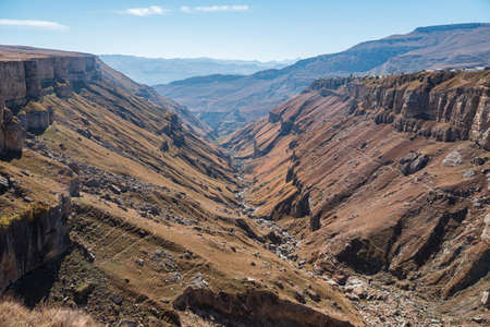 Narrow curving river runs between high hills bare slopes in picturesque deep canyon against mountains under clear blue sky on sunny day