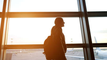 Silhouette of woman with large bag looking out of terminal window at passenger airplanes walks along contemporary airport building Imagens