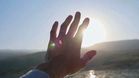 Young man holds hand trying to hide bright shining sun disk in clear blue sky above silhouettes of ancient distant mountains close view