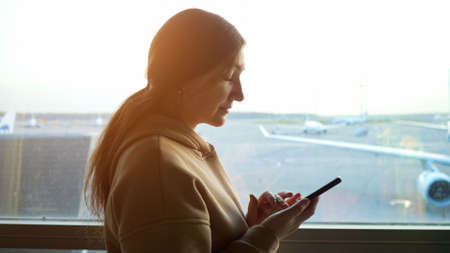 close-up of a young woman with a phone against the background of a window in an airplane view. Imagens