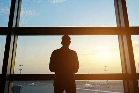 Silhouette of man coming to window to look at new airplanes on large air field in contemporary airport terminal backside view Imagens