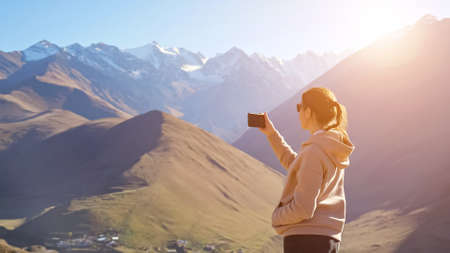 Amazed woman wearing hoodie and sunglasses makes video of breathtaking panorama of beautiful mountain peaks at sunlight using smartphone
