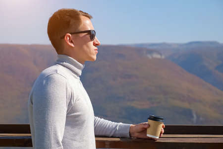 Young man in a gray turtleneck and sun glasses drinks a drink from a plastic glass on a background of mountains on a clear day, sunlight