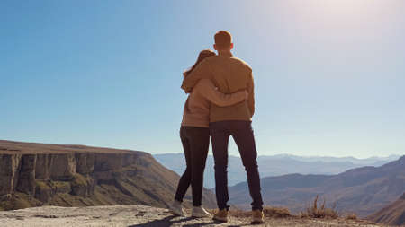 Young couple in love over the cliff admire the view of the valley on a clear sunny day.