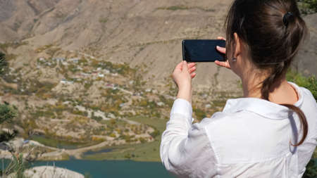 Young woman in white shirt takes picture with phone of green valley with large calm lake among mountains on sunny autumn day close side view Imagens