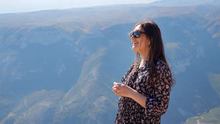 Young woman with sunglasses in stylish dress puts on earphones looking at ancient distant mountains in mist at highland on sunny autumn day
