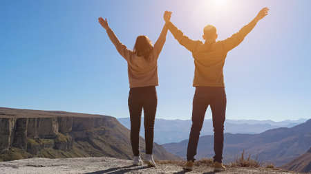 Young couple walks and raises joined hands enjoying view from cliff edge against distant mountains and blue sky on sunny day backside view