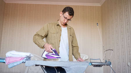 Young man in glasses and shirt ironing things on an ironing board.