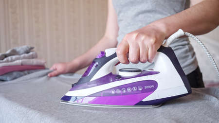 Hardworking woman holding modern purple electric iron irons fast and carefully grey shirt after laundry on special board at home extreme closeup Imagens