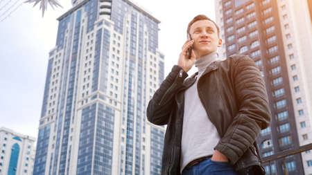 man in a leather jacket talking on the phone against the backdrop of tall houses, copyspace Imagens