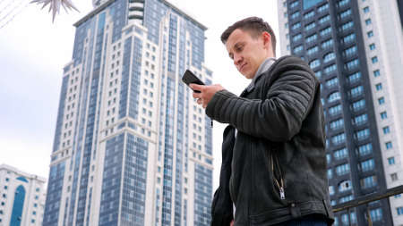 Concentrated handsome man wearing jacket surfs internet in smartphone standing against highrise buildings of residential complex low angle shot