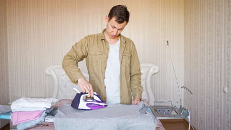 young man ironing things on an ironing board for the first time. Imagens