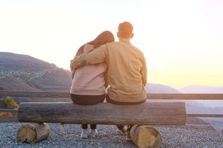 Couple hugs sitting on bench on viewing point against picturesque ancient mountains at sunset backside view