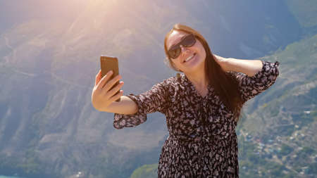 Pretty smiling lady with stylish glasses in loose dress makes selfie against distant ancient mountains at highland on sunny windy day closeup