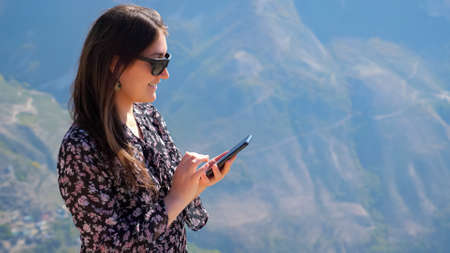 Happy brunette woman with sunglasses in patterned dress uses smartphone against ancient distant mountains at highland on sunny day closeup