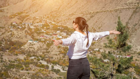 Young woman in white shirt enjoying the view of the valley with her arms spread, rear view.