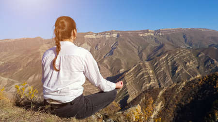 Young brunette woman with plait in white shirt meditates sitting on cliff against distant ancient mountains under clear blue sky backside view
